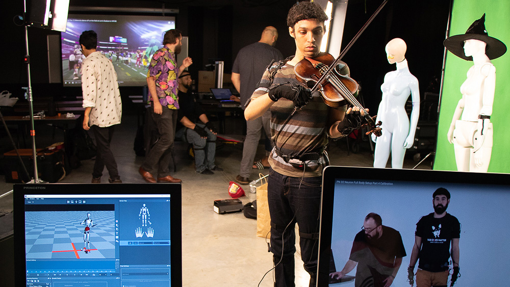 Student playing violin while wearing a motion capture suit in a video production studio