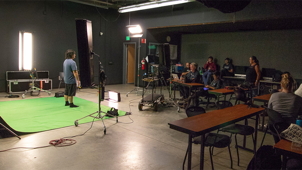 Students in class in the video production studio, with a student standing talking in front of a green screen