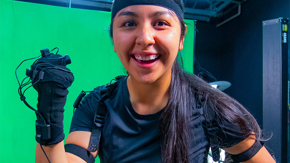 Student smiling in front of a green screen while wearing a motion capture suit
