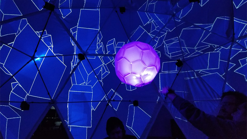 Art installation with people inside a dark room with the walls covered with abstract blue squares and a large floating pink ball in the middle