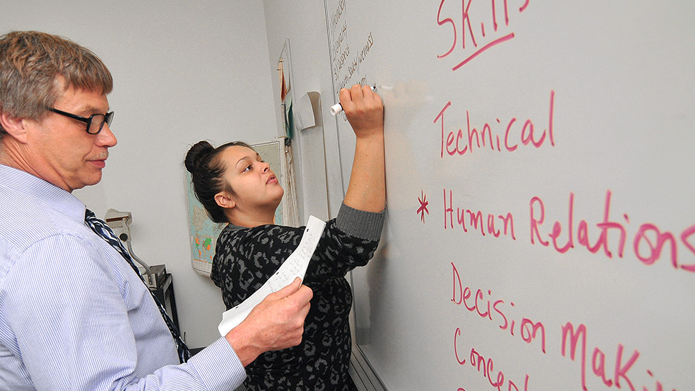 Students writing about job skills on a whiteboard