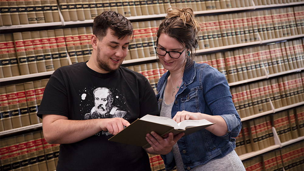 Students looking at a book together in the paralegal library
