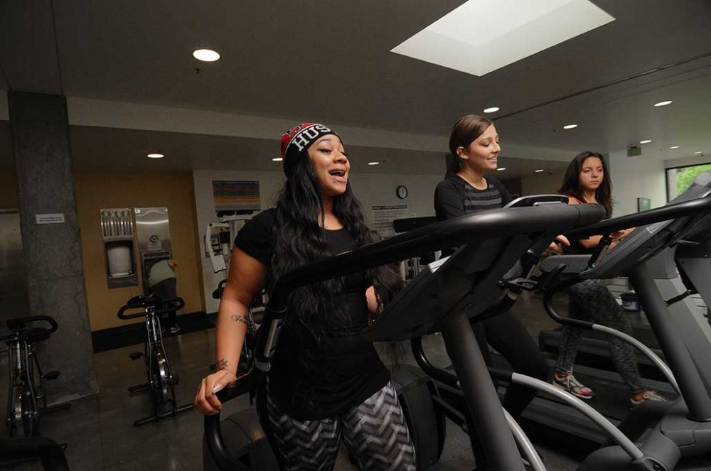 Students walking and running on treadmills in the Cascade Gym loft