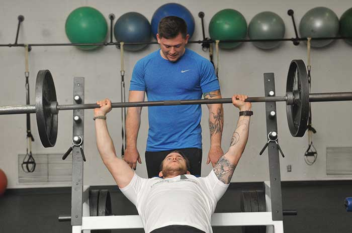 Instructor helping a student weightlift at Sylvania