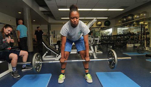 Student lifting weights in a campus fitness and weight room