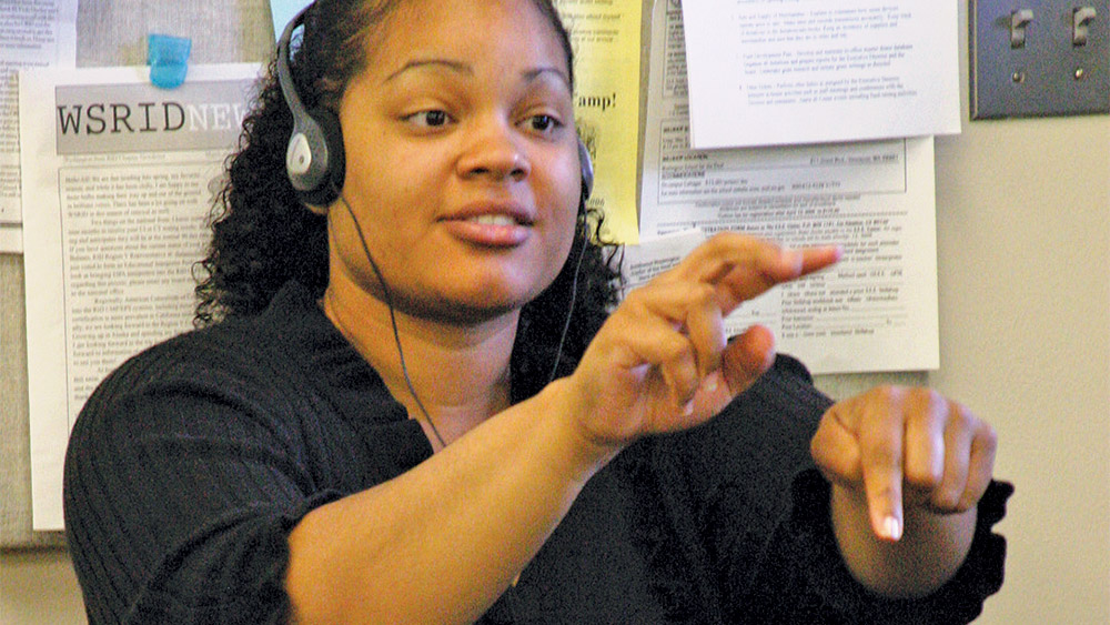 Student practicing sign language in a classroom