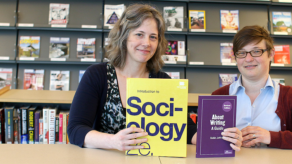 Instructors holding books about sociology