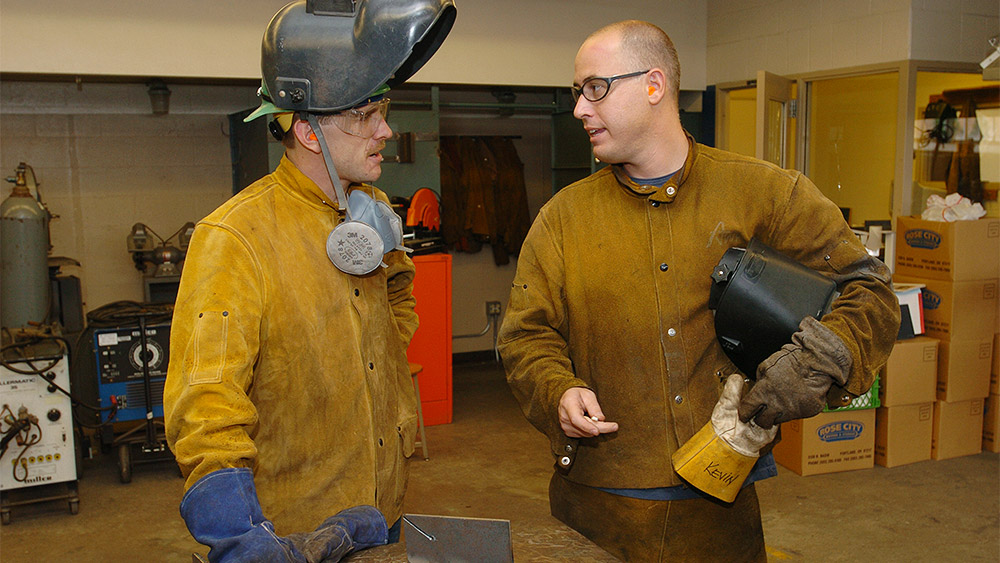 Students talking to each other in the welding shop