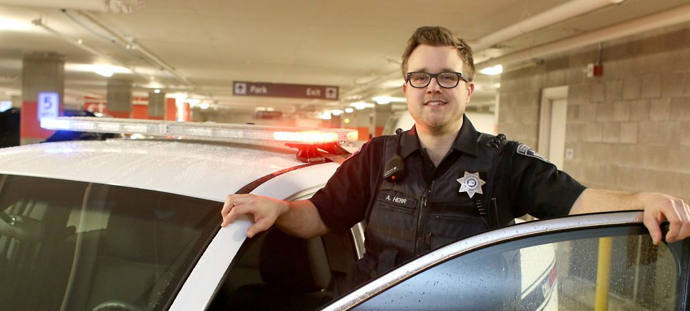 Public safety officer standing next to car