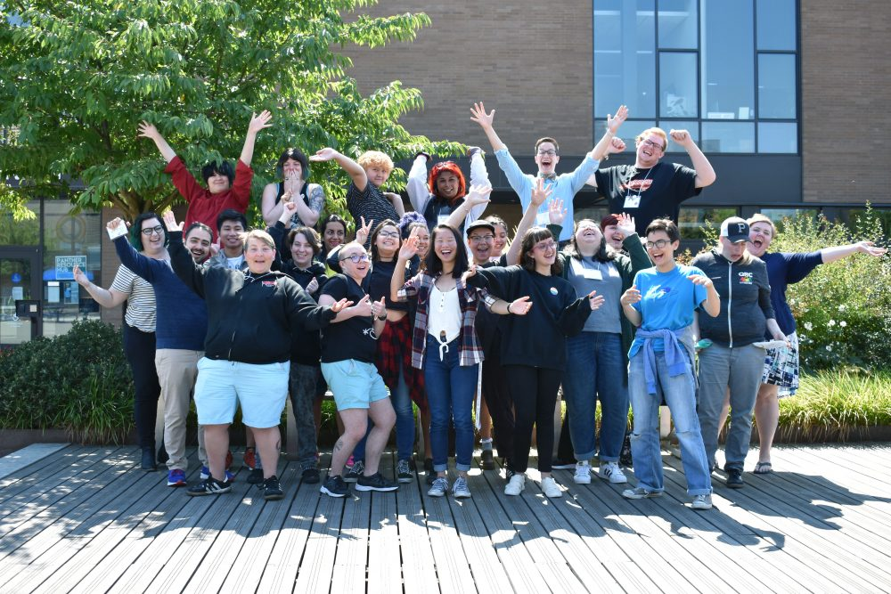 24 QRC student and professional staff members smiling in various high energy poses outdoors.