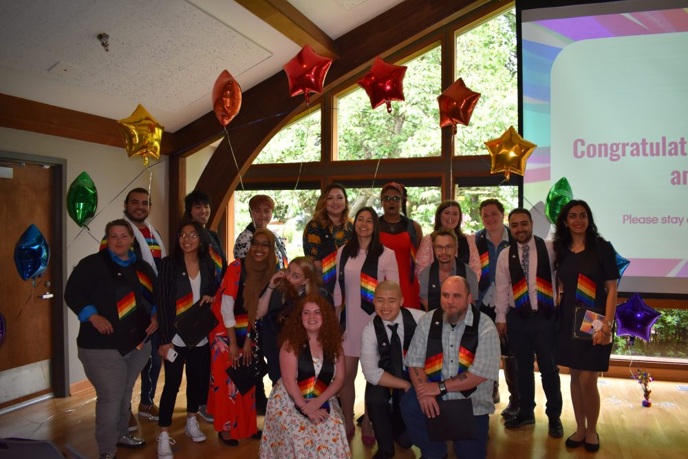 Students at a QRC event with rainbow balloons and sashes