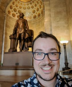 picture of Eric Dodson in front of a statue