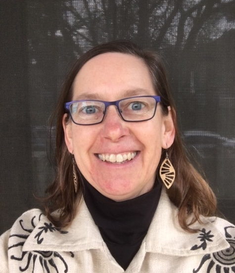 Photo of Julie (woman with fare skin and brown hair wearing blue glasses, light brown earrings, a black turtleneck, and a decorated beige jacket)