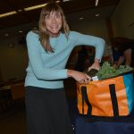 Woman placing items into orange and teal upcycled bag