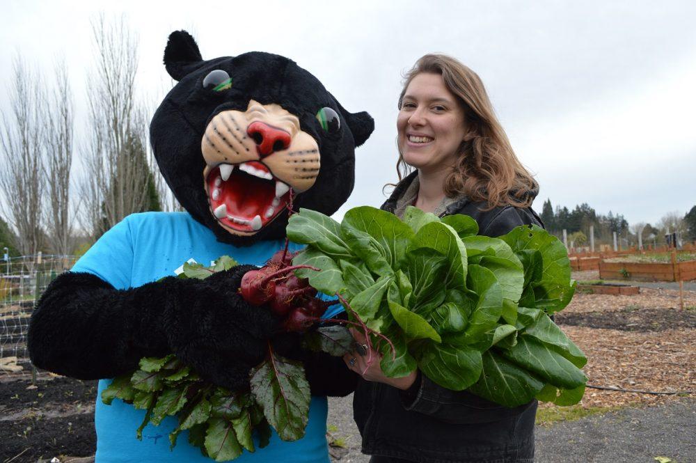 Poppie holding vegetables at the Learning Garden