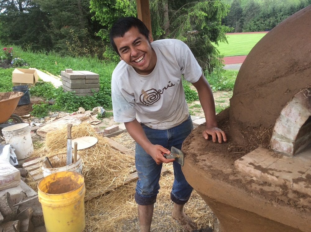Smiling Person building cob oven