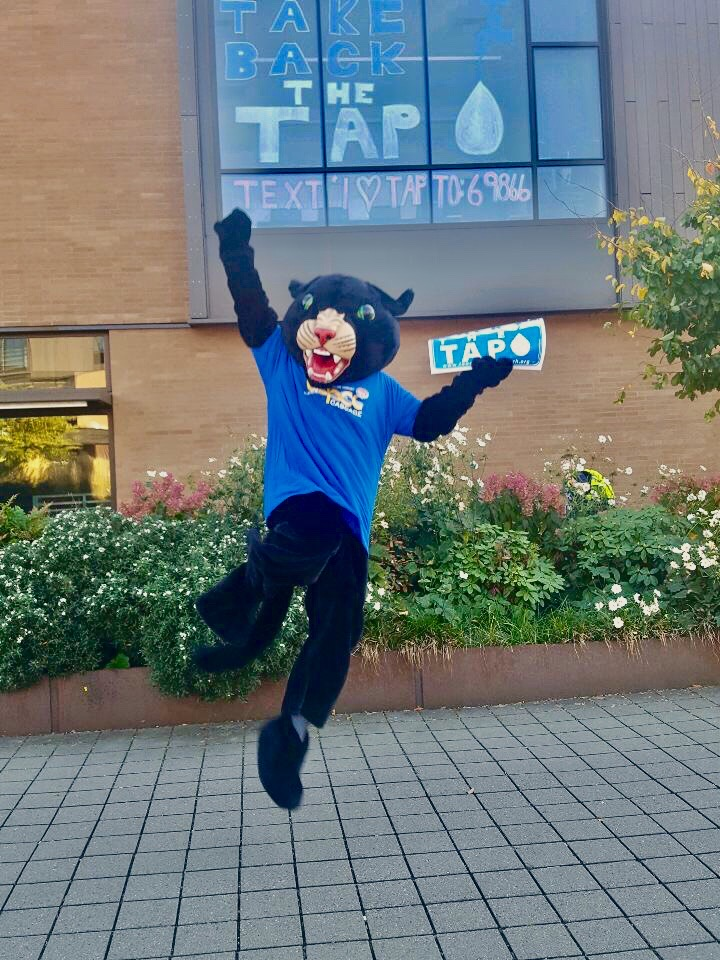 Poppie jumping with Take Back the Tap sign