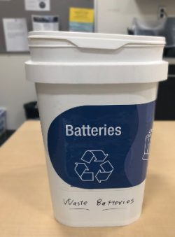 """Recycling bucket, labeled """"batteries""""."""