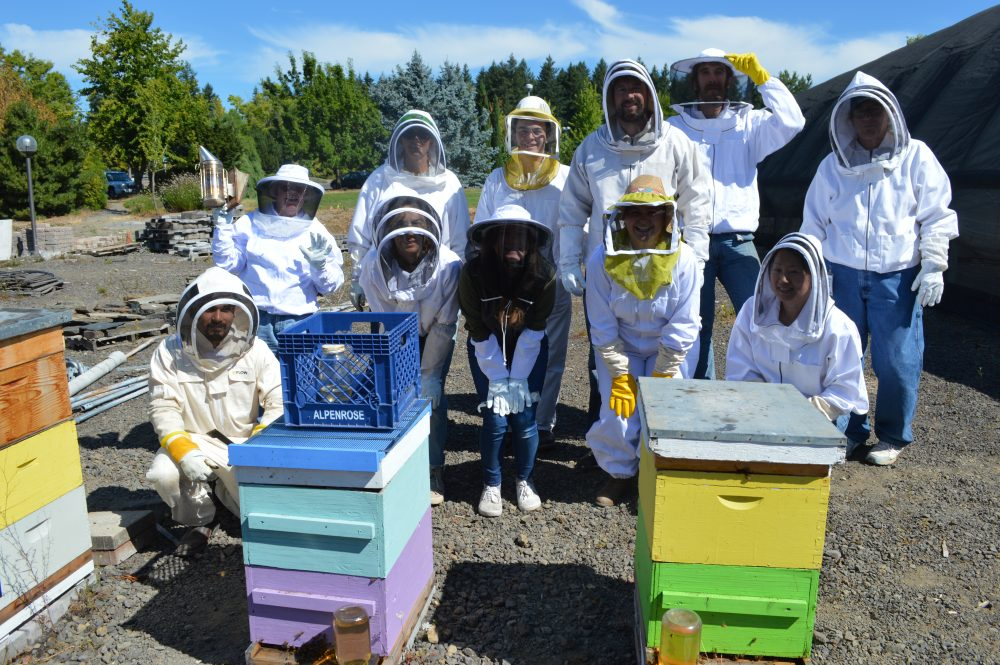 Students in beekeeper suits pose for group photo behind beehives.