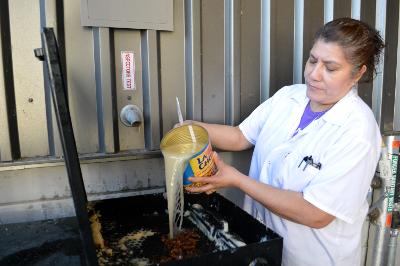 Woman pours fryer oil.
