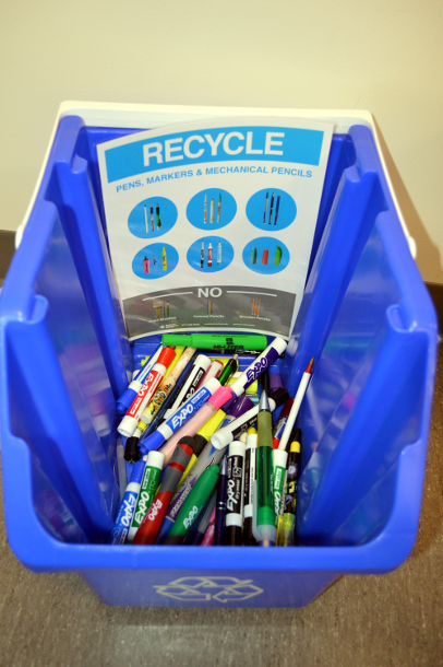 Recycling bucket full of markers and pens.