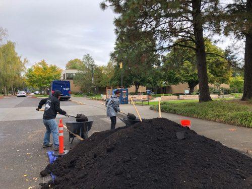 volunteer shovel a big pile of dirt