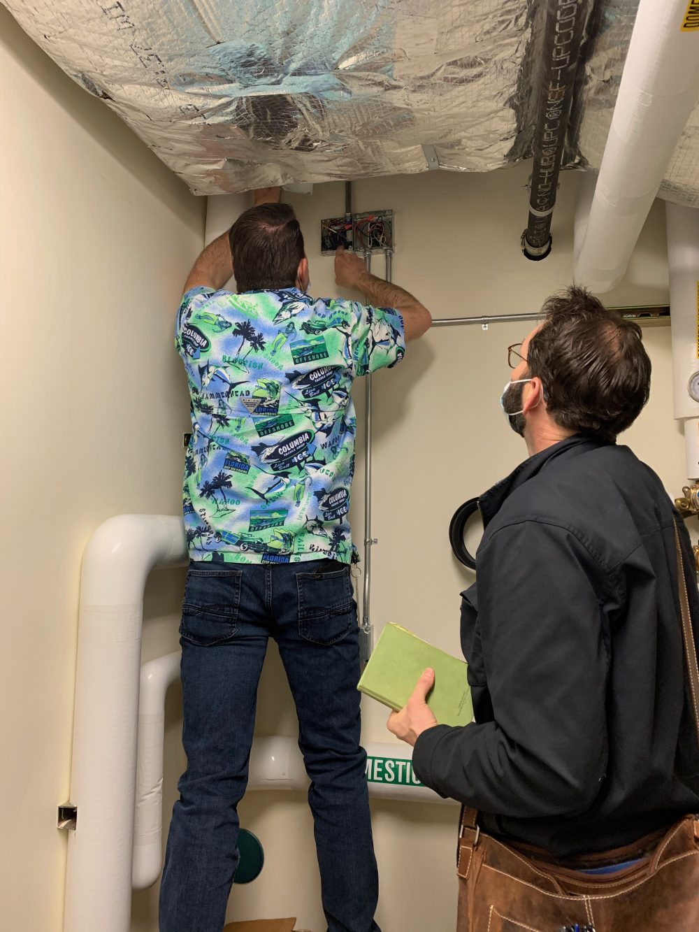 Larry Osborn, FMS Manager, and Dusty Farrell, Energy Trust of Oregon staff, check a domestic hot water relay in the SE Learning Commons Library