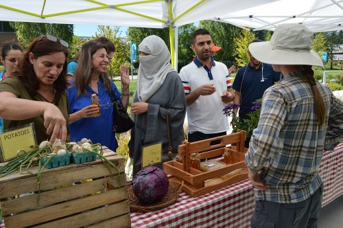 Learning Garden produce stand with people talking