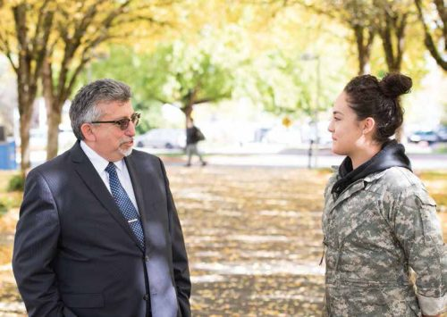 Campus president chats with student in camo coat