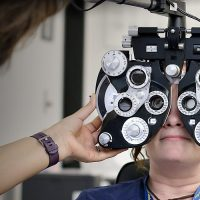Students practicing with eye exam equipment