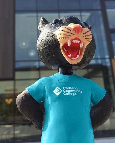 Poppie bobblehead figurine wearing a PCC t-shirt