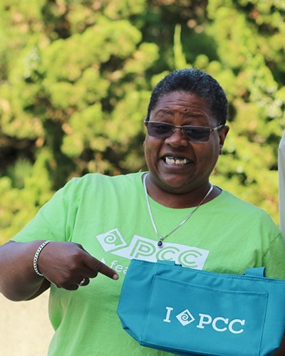 Woman holding PCC tote bag and wearing a PCC t-shirt