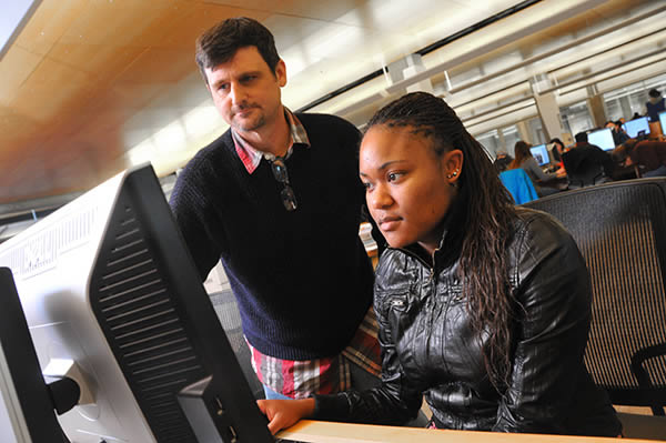 Staff member helping a student at a computer