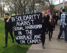 students marching on campus with a poster that says: in solidarity against sexual harassment in the workplace and on campus