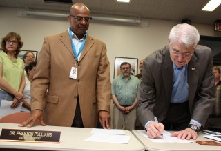 One of his first duties as board chair this year was to sign the new faculty and classified staff labor agreements with District President Preston Pulliams (left).