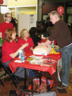 Tim Parsons, a second-year nursing student, demonstrates CPR techniques as interim nursing director Alisa Schneider (left) gives feedback. Holly Hererra (standing) and Karen Christensen (seated) – both second-year nursing students – observe.