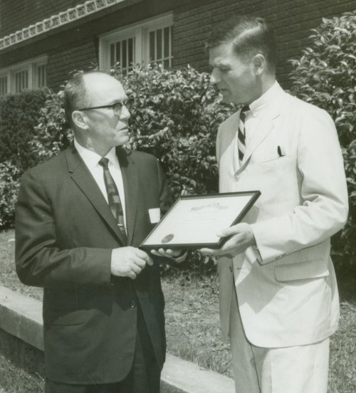 Circa mid-1960s. Founding president Amo DeBernardis (left) poses with young Oregon Governor Mark Hatfield and the college's charter.