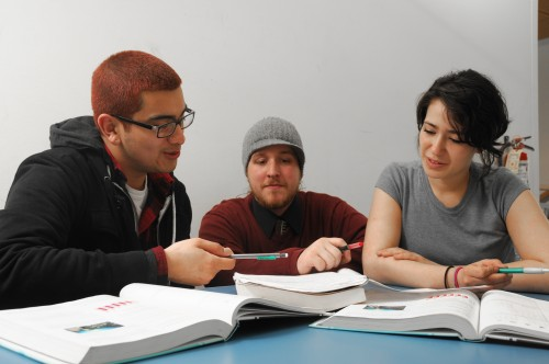 Once expelled from high school, Adam Clark (center) has come full circle and earns a living providing tutoring and technical support for the Gateway to College at the Southeast Center.