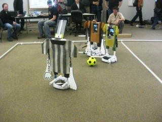 """The remotely-controlled robot soccer players are directed by students and faculty at the computer table on the sidelines. Those commanding the robots' moves can be seen in the tablets – the """"heads"""" of the players."""
