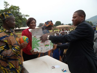 Isaac Sunday hands over his donation to school officials in Awing, Cameroon last fall.