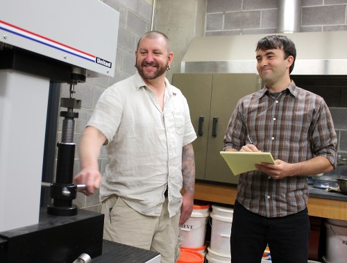 Current student Chad Lane (left) shows Civil & Mechanical Engineering Technology Program advisory board member Luke Levin some of the program's tools of the trade.