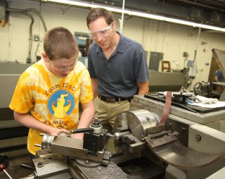 Ben Baldwin, 14, from Catlin Gabel gets a little help from Nathan Beste (right) of FEI Company.
