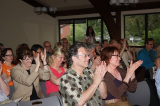 The crowd applauds the board's vote.