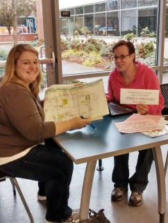 Students Kendal Kelleher and Mindy Cobb analyze the data they have collected from campus faculty and staff.