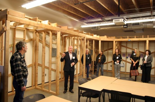 Dan Wenger, Cascade Campus' dean of the Arts & Professions Division, leads a tour of industry leaders. Here, he shows off Swan Island's electrical classroom.