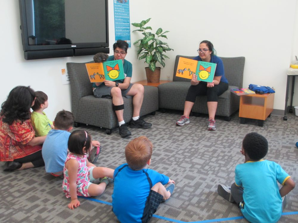 Rut Martínez-Alicea, coordinator for the Multicultural Center (left), listens along with the children from the YMCA childcare center as Farnoosh Khodayar (center) and Elmira Fathe Azam read aloud from a book on diversity. Between six and 10 children attend the story time every Tuesday morning.